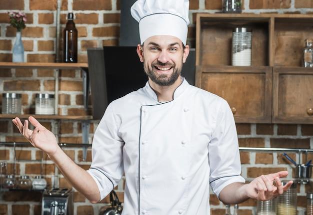 キッチンに立っている男性のシェフが肩をすくめている