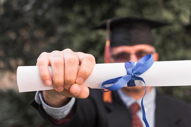認識できない男が卒業証書を見せている