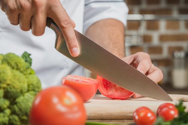 シェフの男性の手は、ボード上の鋭いナイフでトマトを切る