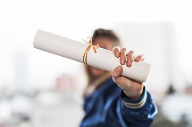 若い女性は卒業証書を示しています