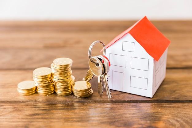 Крупный план сложенных монет, дом и ключ на деревянном столе
