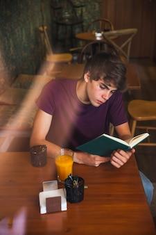 Подросток мальчик, чтение мальчика в хорошем кафе