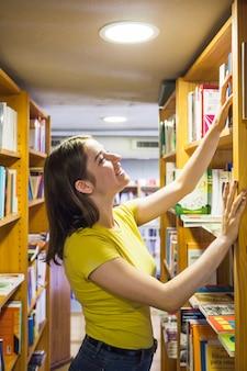 Веселый подросток, выбирающий книгу с полки
