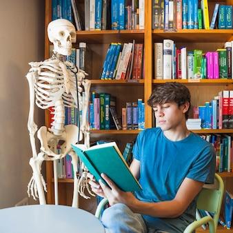 Серьезный подросток читает возле скелета