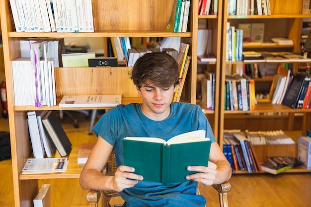 Радостный мужской подросток читает на стуле