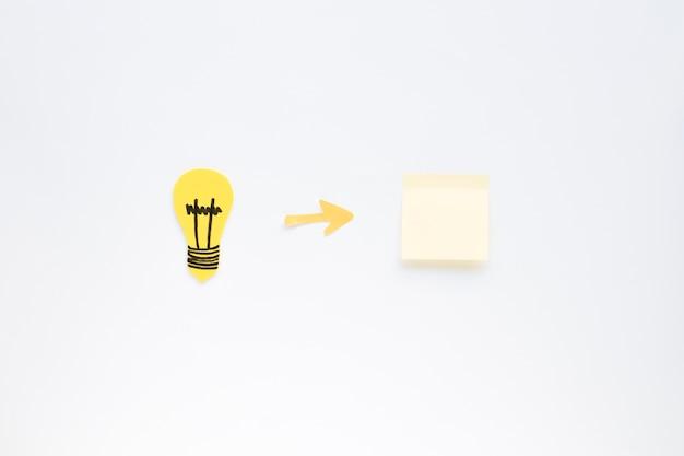 白い背景に電球と粘着ノートの間の矢印記号