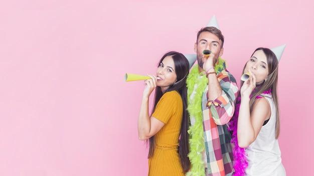 ピンクの背景にパーティーホーンを吹く友人のグループ