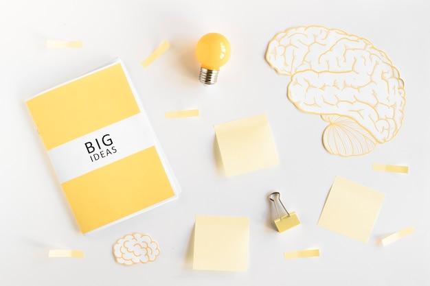 Большой дневник идей, лампочка, мозг и канцелярские принадлежности на белом фоне