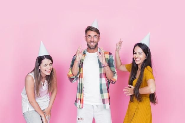 Группа счастливых молодых друзей, с удовольствием на розовом фоне