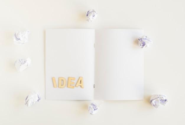 皺のある紙で囲まれたカードのアイデアテキストの高角度図