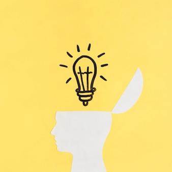 黄色の背景に開いた人間の脳の上に照らされた電球