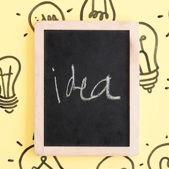 黄色の背景に電球で囲まれたアイデアの言葉と黒いスレート