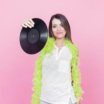 ピンクの背景に手を立ててビニールのレコードを示す緑のボアを身に着けている若い女性