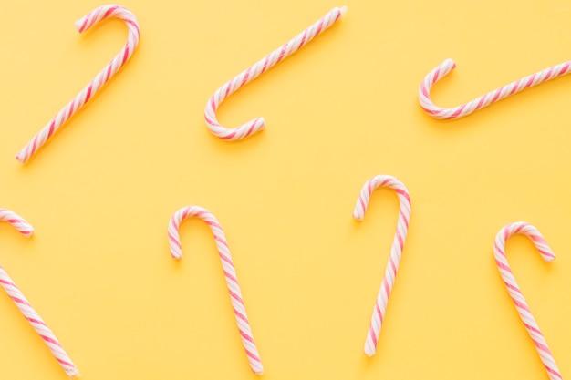 黄色の背景にクリスマスキャンディーの杖