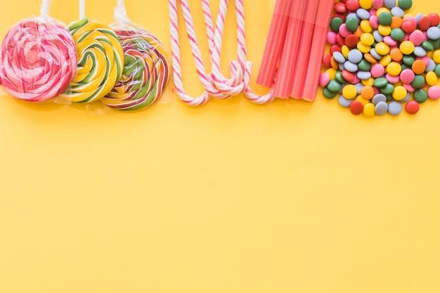 さまざまなカラフルなキャンデー、黄色の背景