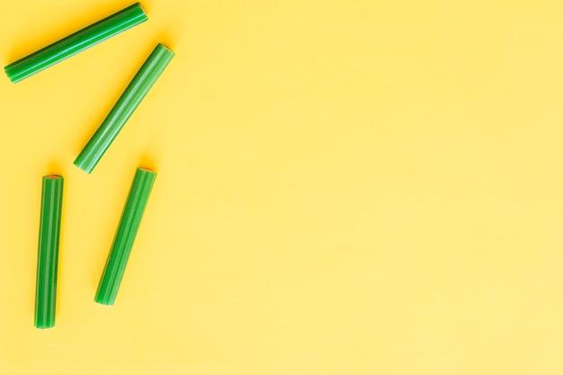 Четыре зеленых мягких лакричных конфет на желтом фоне