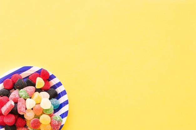 黄色の背景の上にストライププレート上のゼリーキャンディー