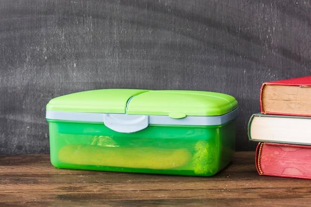 教科書の近くのプラスチック製の弁当箱