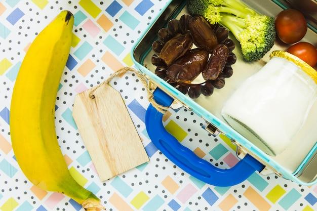 弁当箱の近くに横たわるバナナ
