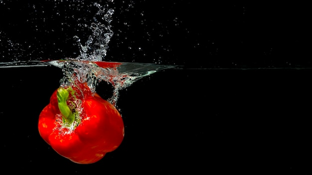 黒の背景の上に水の中に飛ぶ赤いピーマン
