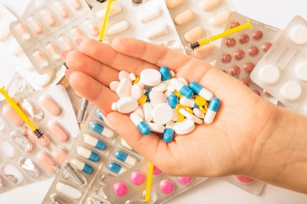 Женщина держит много разных таблеток в руке по блистерной упаковке и шприцу