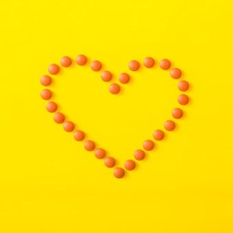 黄色の背景にハート型を形成するオレンジ色の丸薬
