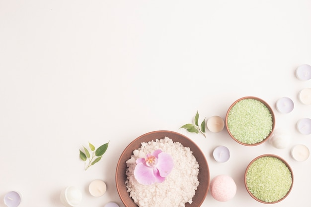 Зеленая и белая травяная морская соль с множеством маленьких свечей на белом фоне