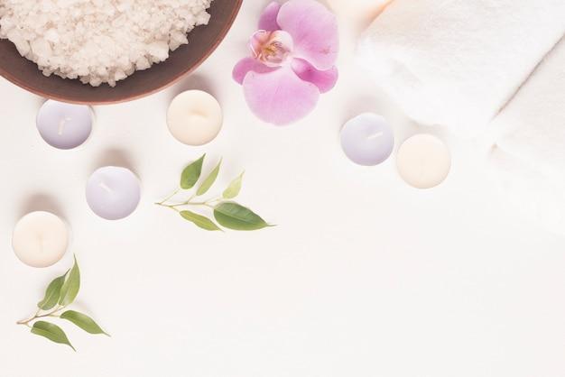Крупный план соли для ванны с орхидеей и свечами на белом фоне
