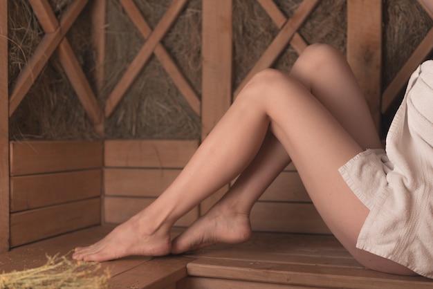 サウナ、ベンチ、セクシーな女性の足のクローズアップ