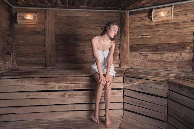木製のサウナでリラックスして座っている女性