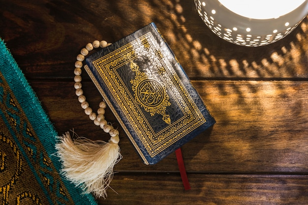 Коран рядом с лампой и ковриком
