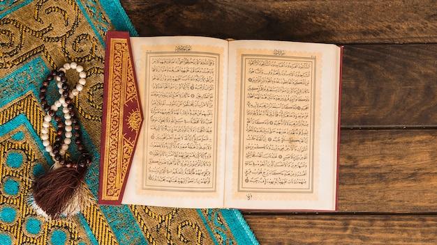 Коран рядом с бусами и узорчатой тряпкой