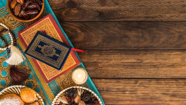 Свеча и сладости рядом с книгами и бусами