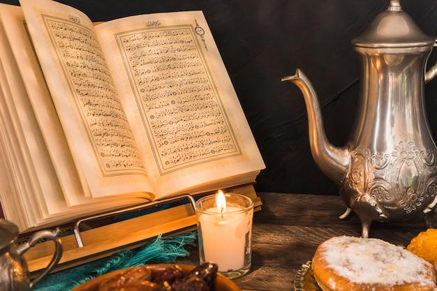 Кондитерские изделия и чайник возле свечи и корана