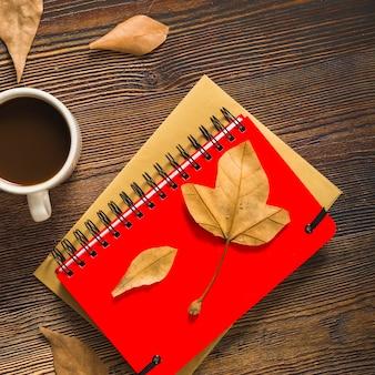 葉と手帳の近くのコーヒー