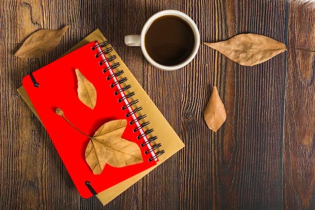 メモ帳の近くの葉とコーヒー