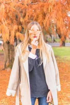 秋の葉を見下ろすブロンドの女性