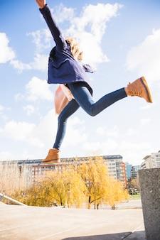 秋の公園の下で飛んでいる女性