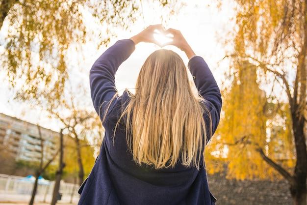 Безликая модель, показывающая сердце солнцу