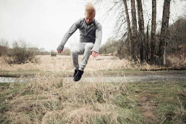 干草草の上をジャンプする若い男