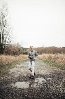 Мужской бегун останавливается возле лужи, бегая по грунтовой дороге в поле