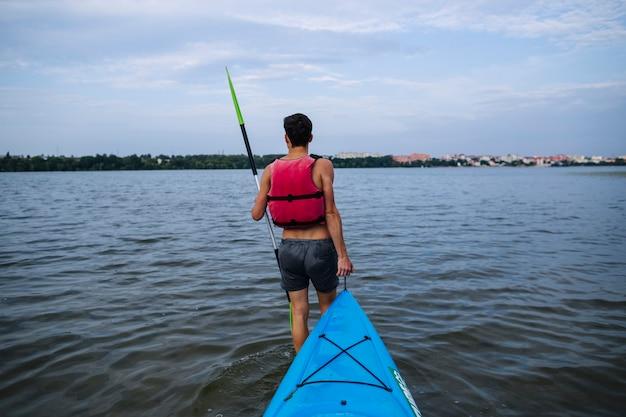 牧歌的な湖で青いカヤックを運んでいる男