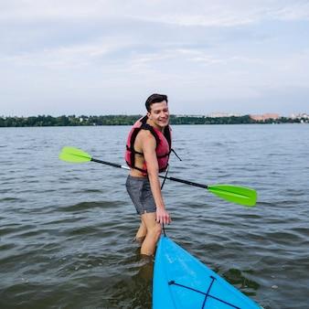 湖でカヤックを引っ張っている笑顔の若い男