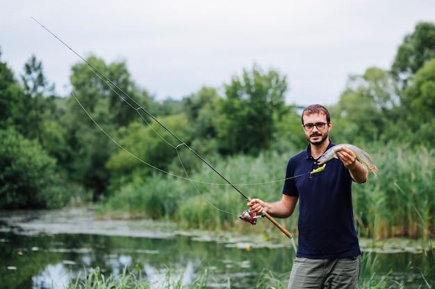 湖の前に立っている男が新鮮な魚を捕まえた