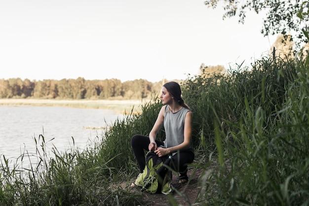 湖の近くに身をかがめる彼女のバックパックとフィットネス若い女性