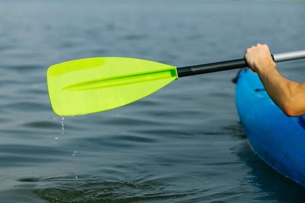 人は牧歌的な湖の上でカヤックを漕ぐ