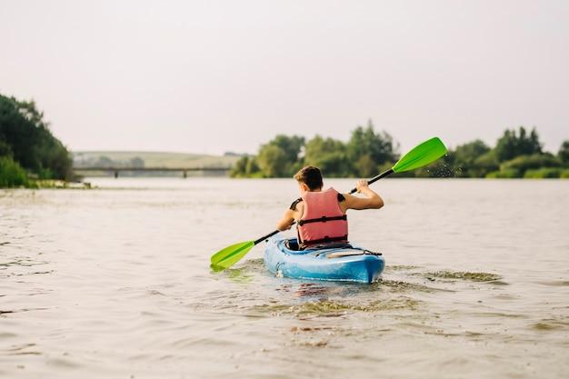 パドルで湖でカヤックをする男