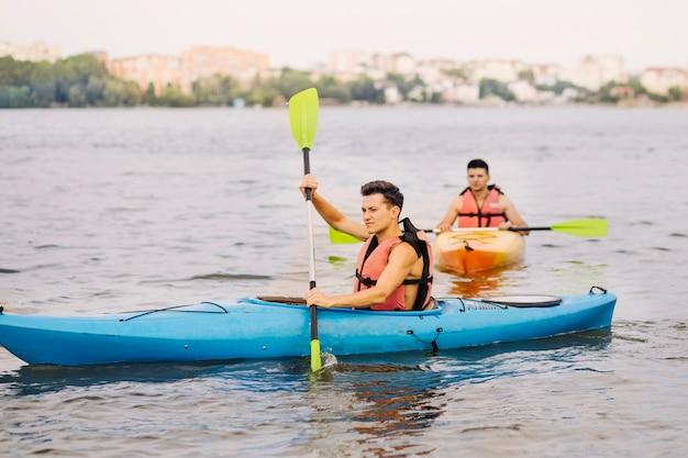 彼の友人と湖でカヤックをする男