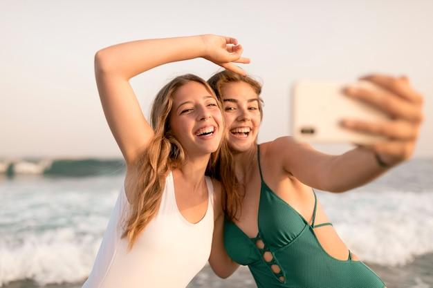 Счастливые женщины-друзья, берущие себя из смартфона на берегу моря