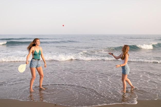 Две девушки играют в теннис на берегу моря